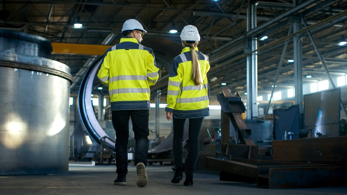 Two workers seen from the back in an industrial environment