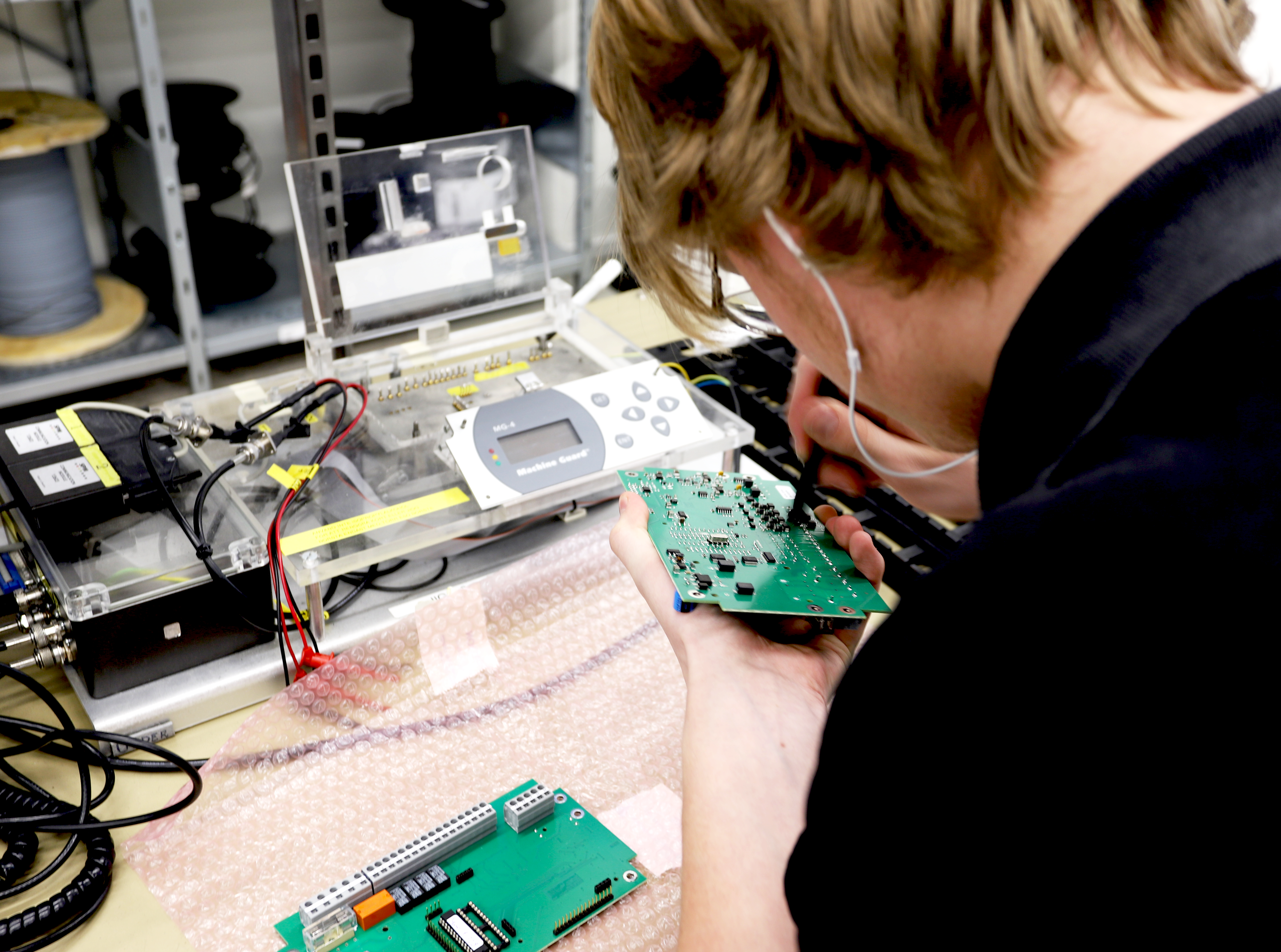 Electronics technician soldering on a circuit board